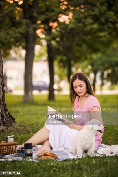 giovane donna godendo i suoi momenti di solitudine nel parco - dog pad foto e immagini stock