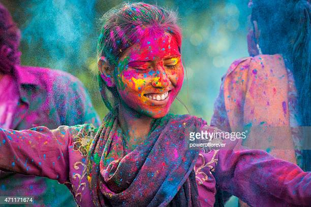 young woman enjoying holi festival - holi stock pictures, royalty-free photos & images