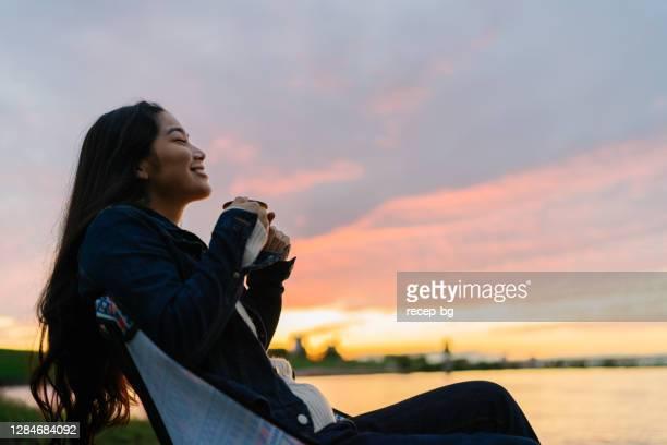 湖の夕日の間に自然の中で熱い飲み物を楽しむ若い女性 - キャンプ 1人 ストックフォトと画像