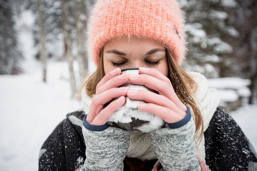 Young woman enjoying hot drink outdoors in winter - gettyimageskorea