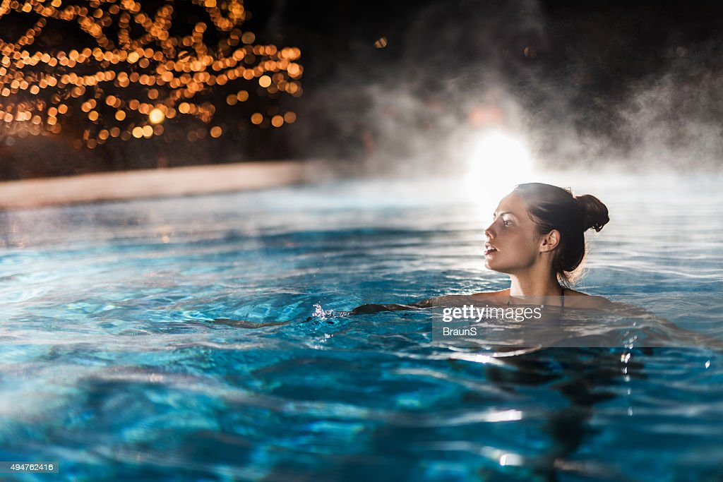 Young woman enjoying in a heated swimming pool at night. : Stock Photo
