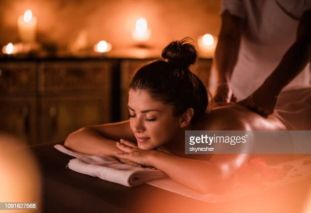 young woman enjoying in relaxing moments of a massage at health spa. - massage therapist stock pictures, royalty-free photos & images