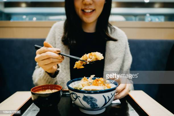 young woman enjoying japanese cuisine, tempura donburi with miso soup in restaurant - tendon stock photos and pictures