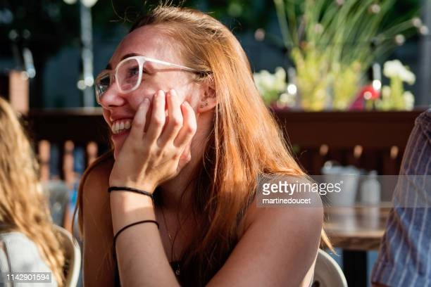 Young woman enjoying leisure time at restaurant terrace.