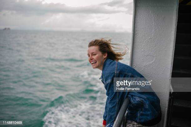 young woman enjoying life on ferry - fähre stock-fotos und bilder