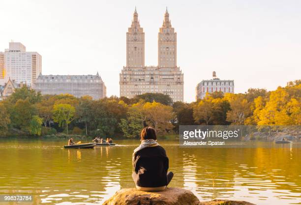 Young woman enjoying New York skyline and autumn colors in Central Park, NY, USA