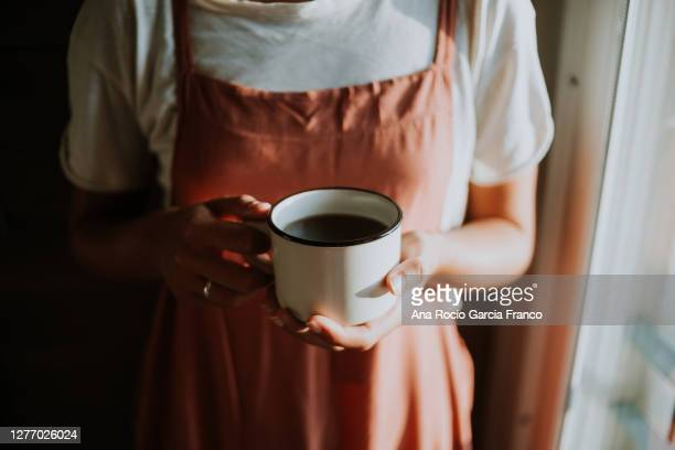 a young woman enjoying of a mug of tea at home - steeping stock pictures, royalty-free photos & images
