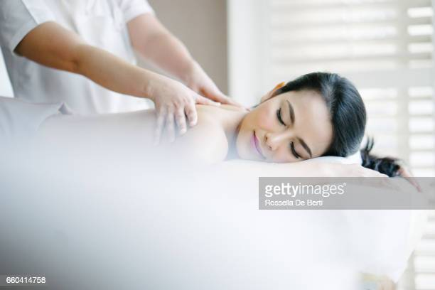 young woman enjoying oil massage - beauty care occupation stock photos and pictures