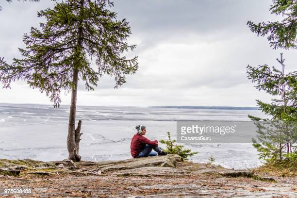 young woman enjoying, relaxing and observing the view of lake - tampere finland stock pictures, royalty-free photos & images
