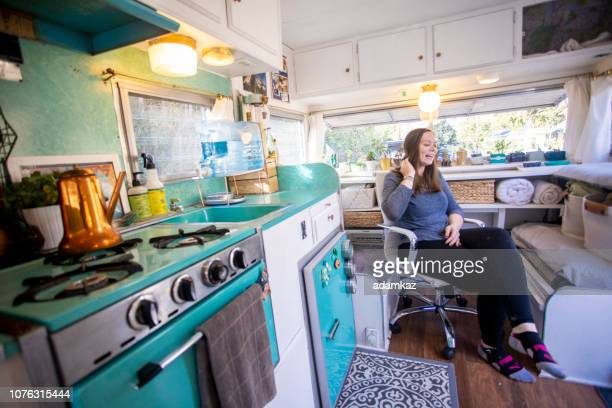 Young woman enjoying sitting in her RV at camp