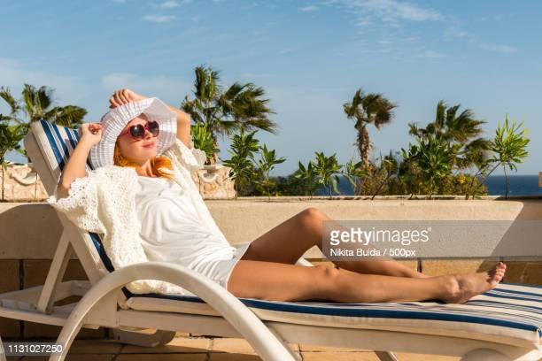 young woman enjoying sun - sun lounger stock pictures, royalty-free photos & images