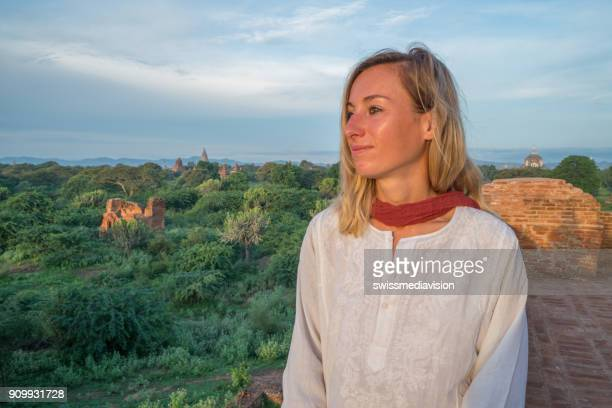 Young woman enjoying sunrise in Bagan ancient temples complex area, Myanmar