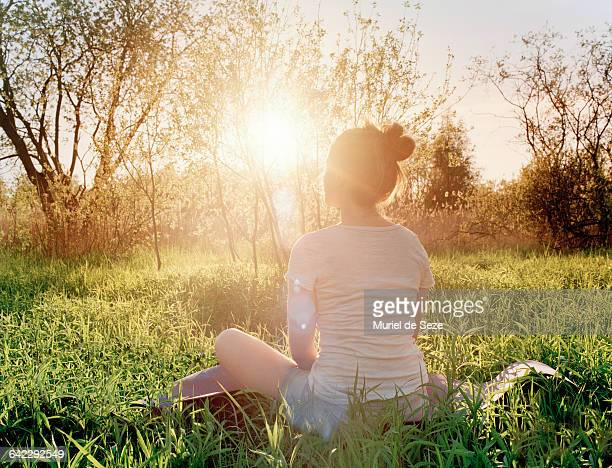young woman enjoying sunset - spiritualiteit stockfoto's en -beelden
