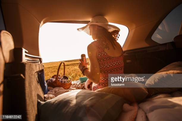 young woman enjoying sunset while camping in the back of her vehicle - hamper stock pictures, royalty-free photos & images