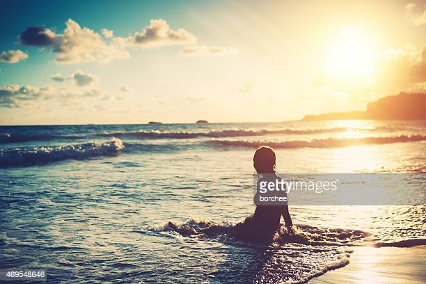 Young Woman Enjoying Sunset While Sitting In The Water