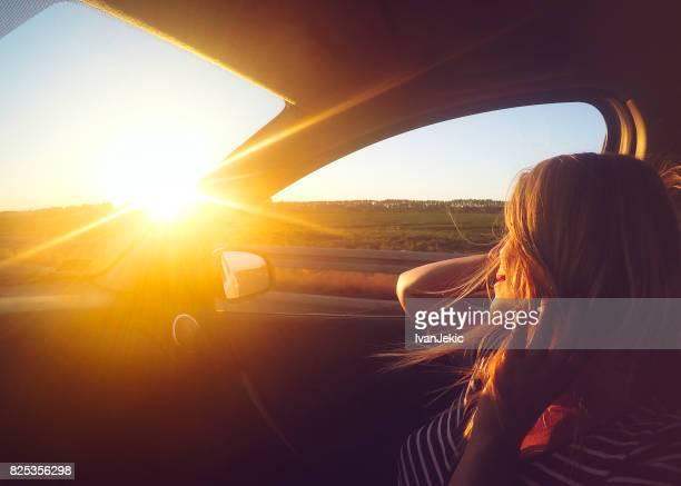 Young woman enjoying the car ride at sunset