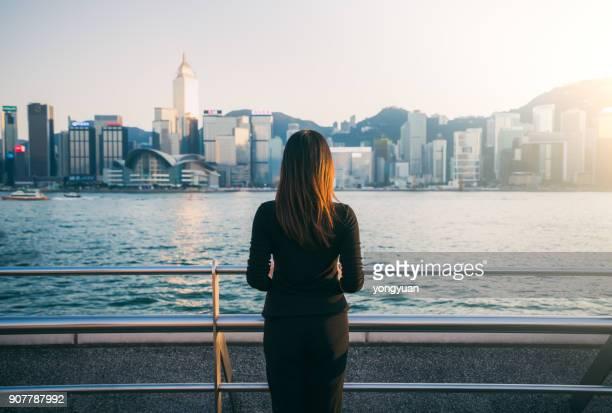 jeune femme appréciant le paysage urbain - femme brune de dos photos et images de collection