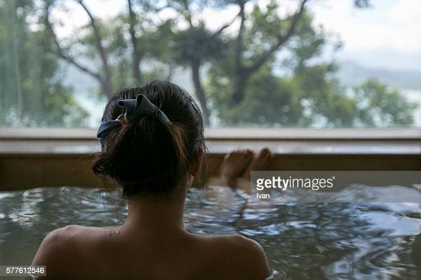 A Young Woman Enjoying the Japanese Style Hot Spring Waters with Beautiful Landscape View