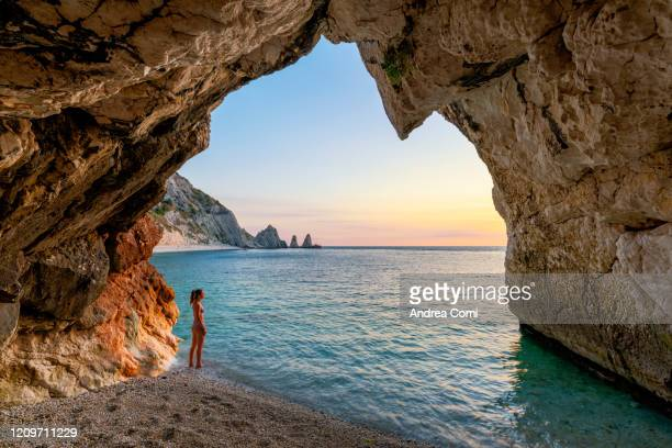 young woman enjoying the sunrise from a cave at two sisters beach (le due sorelle). conero, italy - mediterranean culture stock pictures, royalty-free photos & images
