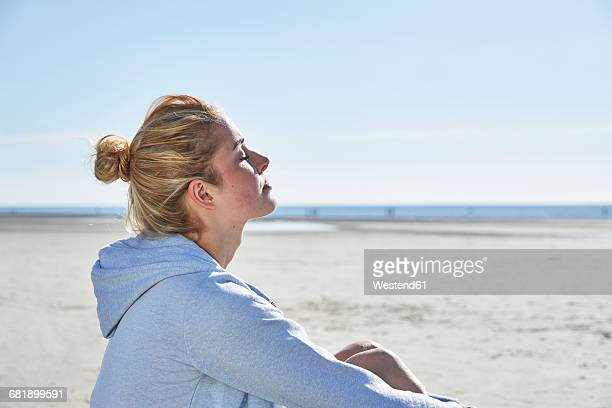 Young woman enjoying the sunshine on the beach