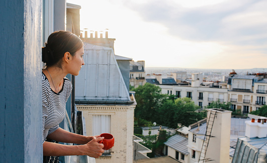 Young woman enjoying the view from a Parisian apartment - gettyimageskorea