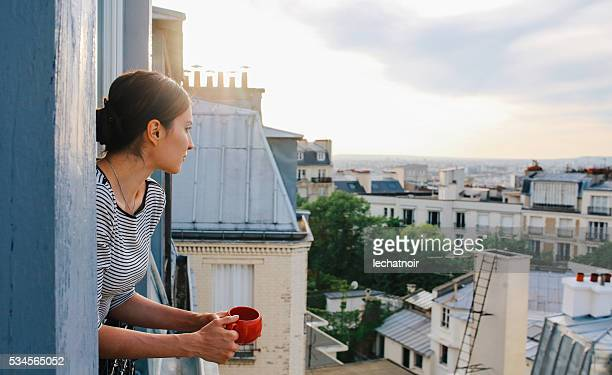 young woman enjoying the view from a parisian apartment - france stock pictures, royalty-free photos & images