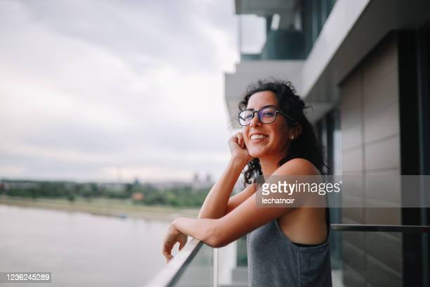 young woman enjoying the view on her balcony - mid adult stock pictures, royalty-free photos & images