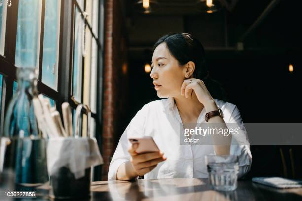 young woman enjoying the warmth of sunlight and having a relaxing time in cafe - photo messaging stock pictures, royalty-free photos & images