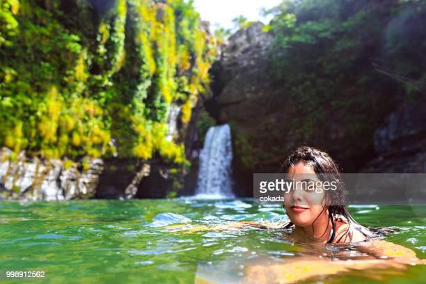 Junge Frau, die den Wasserfall Rei Do Prata, Chapada Dos Veadeiros genießen