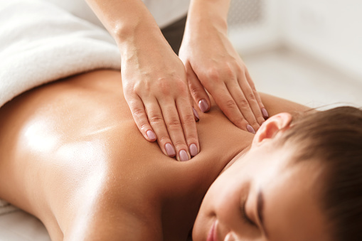 Young woman enjoying therapeutic neck massage in spa 1175433234