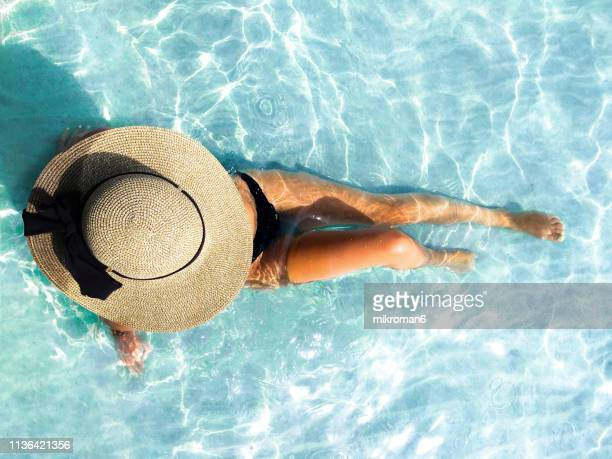 young woman enjoying time on the beach in tropical country - women sunbathing stock photos and pictures