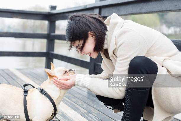 young woman enjoying time with her dog in park - chinese bulldog stock pictures, royalty-free photos & images