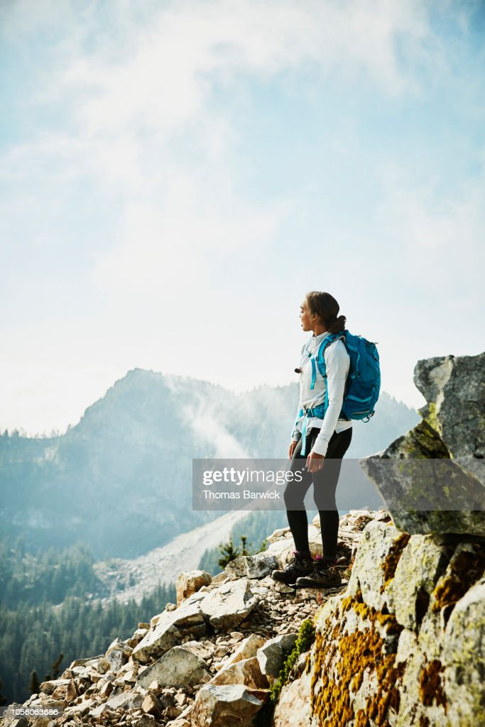 Young woman enjoying view from outlook during hike in mountains : Stock Photo