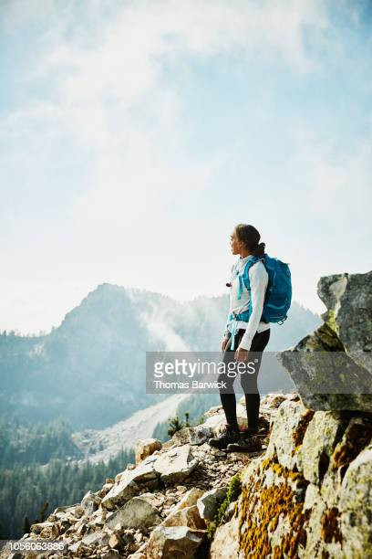 Young woman enjoying view from outlook during hike in mountains