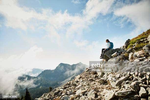young woman enjoying view while sitting on rock during hike in mountains - majestoso - fotografias e filmes do acervo