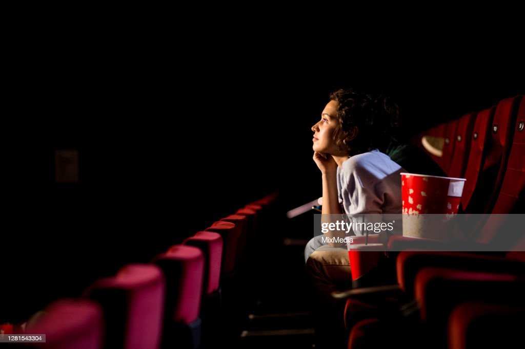 Jonge vrouw die van het letten van film bij de bioskoop geniet : Stockfoto