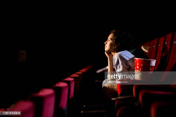 young woman enjoying watching movie at the cinema - film industry stock pictures, royalty-free photos & images