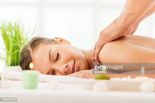 Young woman enjoying while receiving back massage.