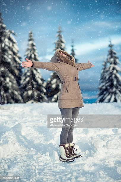 Young Woman Enjoying Winter with Raised Arms While Snowing