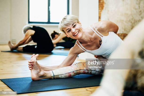 young woman enjoying yoga class - leisure equipment stock pictures, royalty-free photos & images