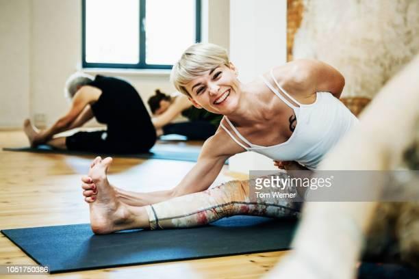 young woman enjoying yoga class - yoga stock-fotos und bilder