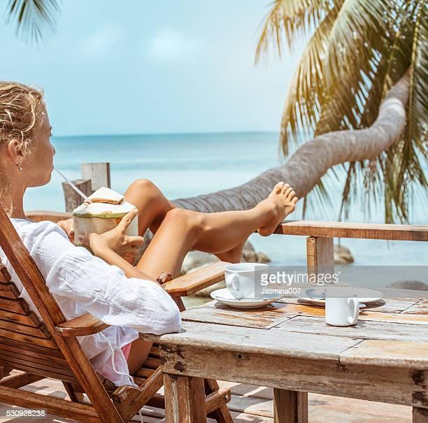 Junge Frau bietet trinkt Kaffee und Kokosnuss verwendet.