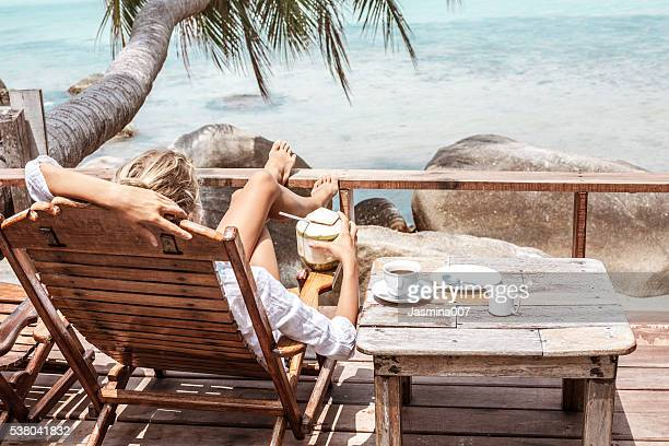 Mujer joven bebiendo café y coco ofrece