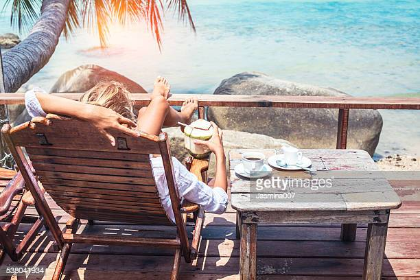 young woman enjoys drinking coffee and coconut - travel destinations stock pictures, royalty-free photos & images