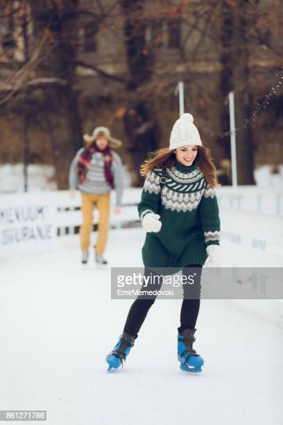 Young woman enjoys ice-skating on a winter day.