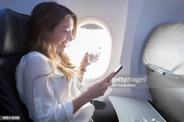 young woman enjoys in flight beverage and wifi - aeroplane stock photos and pictures