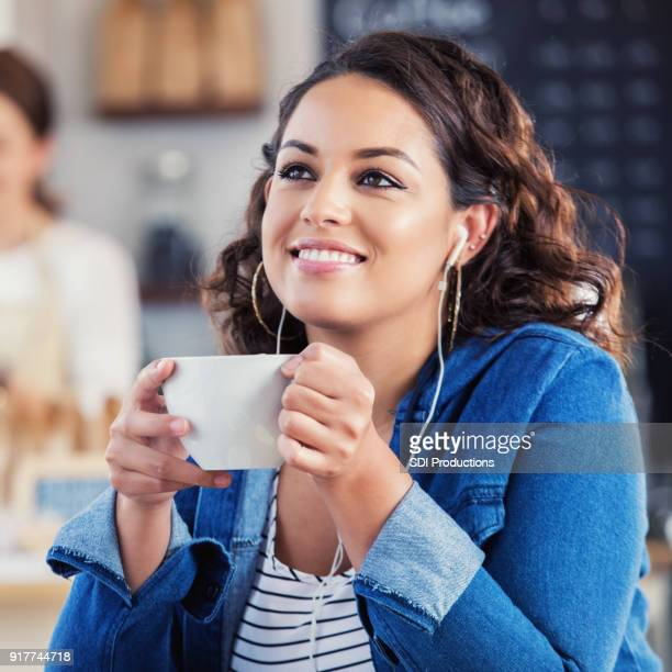 young woman enjoys music during coffee shop break - one young woman only stock pictures, royalty-free photos & images