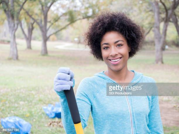 young woman enjoys outside cleanup - green glove stock photos and pictures