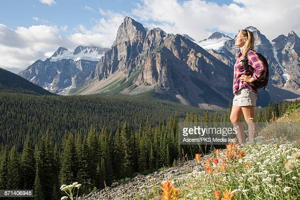 young woman enjoys sun on mountainside, hiking - hand on hip stock pictures, royalty-free photos & images