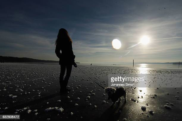 A young woman enjoys the sun walking her dog on Lake Ammersee on January 28 2017 in Stegen am Ammersee Germany After an unusual cold winter period...